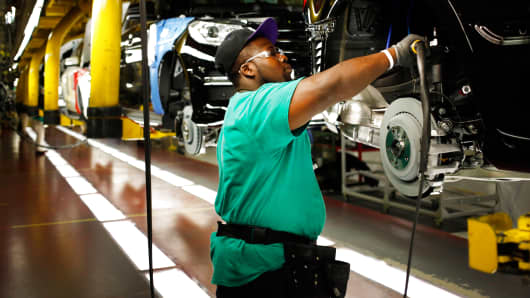 A worker uses a tool on a Daimler AG Mercedes Benz M-Class vehicle at the company's international assembly plant in Vance, Alabama, May 28, 2014.