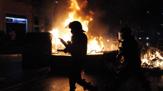 Riot police walk past burning bin containers on the third night of clashes with demonstrators following the evictions of activists from the 'Can Vies' social centre.