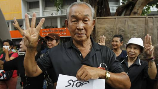 Protesters against military rule make the three fingered salute from the movie The Hunger Games, during a brief demonstration in Bangkok. According to some, the three fingered gesture stood for freedom, equality and brotherhood.