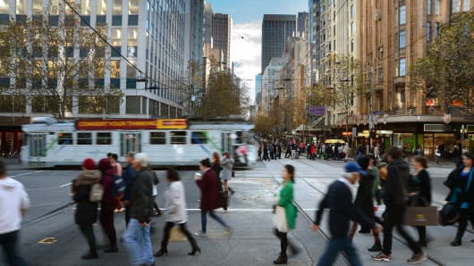 Pedestrians cross an intersection at Collins Street and Swanston Street in central Melbourne, Australia.