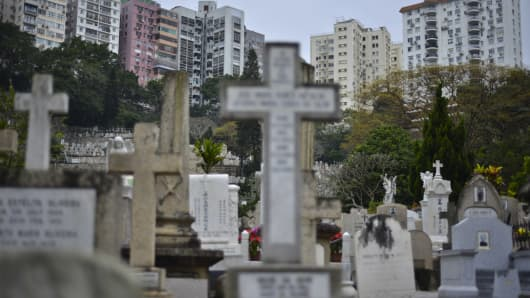 Head stones adorn graves in a Catholic cemetery below residential buildings in Hong Kong.
