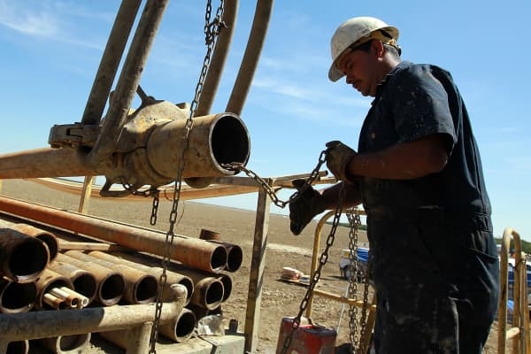 A worker prepares to install a new pipe on a rig while drilling a new well at a farm on April 29, 2014 near Mendota, California.