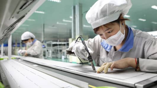Employees work on a solar panel production line at Shenzhou New Energy Co., Ltd on August 27, 2012 in Lianyungang, China.