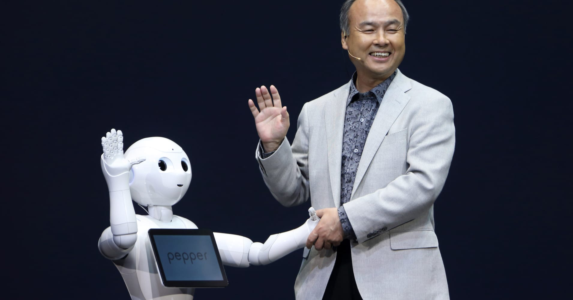 Billionaire Masayoshi Son, chairman and chief executive officer of SoftBank Corp., shakes hands with a human-like robot called Pepper, developed by the company's Aldebran Robotics unit, during a news conference in Urayasu, Chiba Prefecture, Japan.