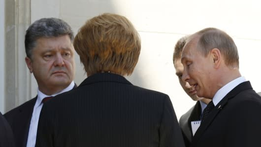 Ukraine president-elect Petro Poroshenko (left), German Chancellor Angela Merkel (center) and Russian President Vladimir Putin talk after a group photo during the 70th anniversary of the D-Day landings in Benouville, France.