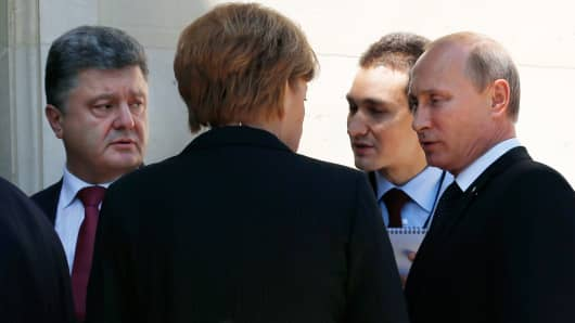 Ukraine president-elect Petro Poroshenko (L), German Chancellor Angela Merkel (C) and Russian President Vladimir Putin talk after a group photo during the 70th anniversary of the D-Day landings in Benouville, France June 6, 2014.