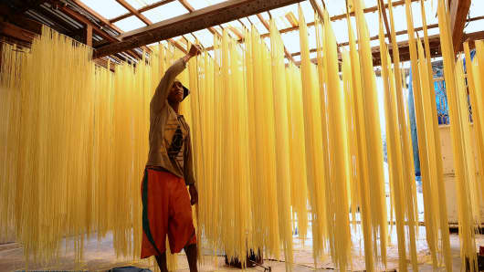 A worker leaves traditional, long noodles to dry in the sun in Singkawang, Kalimantan, Indonesia.
