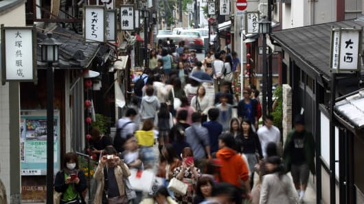 Pedestrians and tourists walk along a street in Kyoto, Japan.