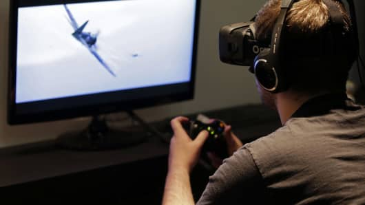 A gamer wears a high-definition virtual reality (VR) headset, manufactured by Oculus VR Inc.