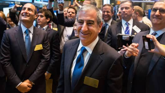 Chief executive officer of Moelis & Co., Ken Moelis (C), smiles after ringing the bell to mark the company's IPO on the floor of the New York Stock Exchange, April 16, 2014.