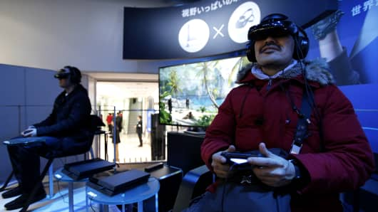 Visitors play video games on Sony Computer Entertainment Inc. PlayStation 4 (PS4) video game consoles during a preview event at the Sony showroom in Tokyo, Japan.