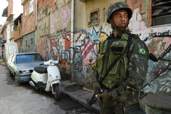 A soldier stands guard in a shantytown complex near Rio de Janeiro airport ahead of the World Cup