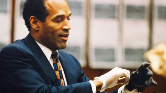 O.J. Simpson tries on a leather glove allegedly used in the murders of Nicole Brown Simpson and Ronald Goldman during testimony in Simpson's murder trial on June 15, 1995 in Los Angeles.