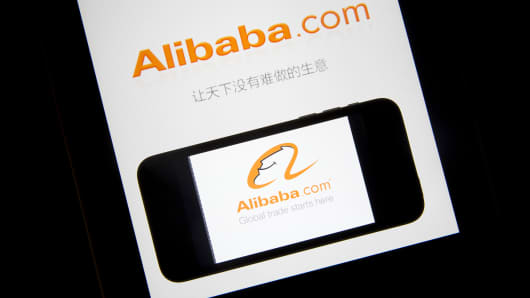 The Alibaba Group Holding Ltd. application loading page is displayed on an Apple Inc. iPad, rear, and iPhone 5s in an arranged photograph.
