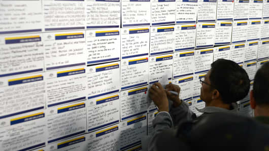A job seeker takes notes as he browses job notices at a jobs and skills expo run by the Australian government in Melbourne, Australia.