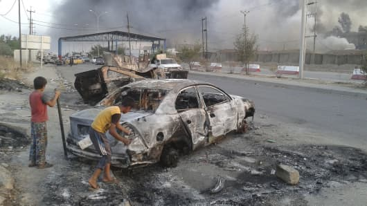 DATE IMPORTED:June 10, 2014Civilian children stand next to a burnt vehicle during clashes between Iraqi security forces and al Qaeda-linked Islamic State in Iraq and the Levant (ISIL) in the northern Iraq city of Mosul, June 10, 2014.