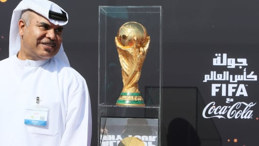 A Qatari official stands near the FIFA World Cup trophy following its arrival in Doha.