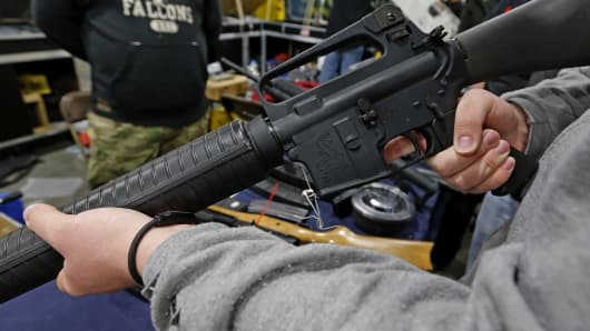 A man holds a Bushmaster AR-15 Model A2 semi-automatic assault rifle.