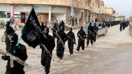 This undated file image posted on a militant website on Tuesday, Jan. 14, 2014 shows fighters from the al-Qaida linked Islamic State of Iraq and the Levant (ISIL) marching in Raqqa, Syria.