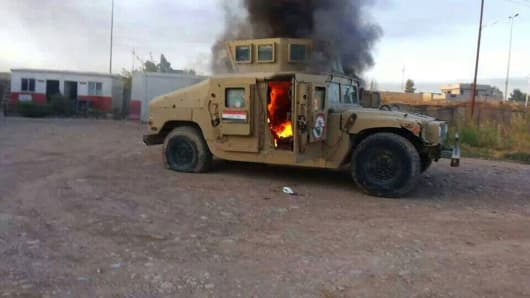 An armored vehicle belonging to Iraqi security forces is in  flames after hundreds of militants launched a major assault.