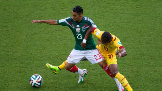 Enoh Eyong of Cameroon challenges Jose Juan Vazquez of Mexico in the first half during the 2014 FIFA World Cup Brazil Group A match between Mexico and Cameroon at Estadio das Dunas on June 13, 2014 in Natal, Brazil.
