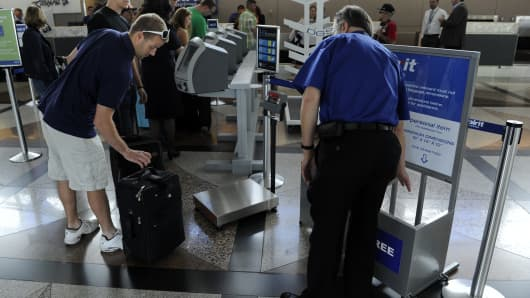 A Spirit Airlines employee demonstrating the airlines carry-on baggage template.