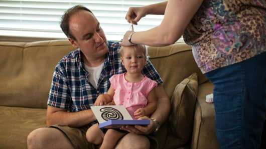 Corey Fontenot holds his daughter Cora as his wife Donna puts her hair in a ponytail.