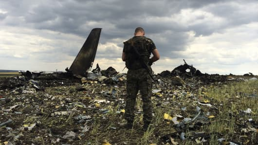 A pro-Russian fighter guards the site of remnants of a downed Ukrainian army aircraft Il-76 at the airport near Luhansk, Ukraine, Saturday, June 14, 2014. Pro-Russian separatists shot down the military transport plane Saturday in the country's restive east, killing all 49 service personnel on board, Ukrainian officials said.