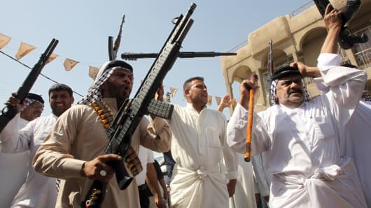 Iraqi tribes men carry their weapons as they gather, volunteering to fight along side the Iraqi security forces against Jihadist militants.
