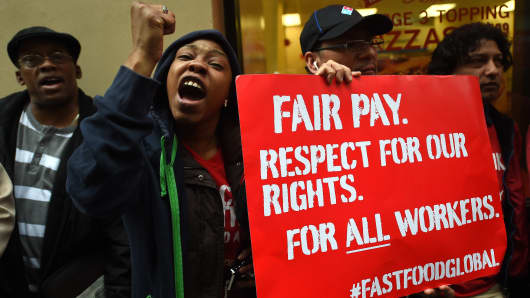 Fast-food workers hold placards in support to an increase of the fastfood workers minimun wage in New York.