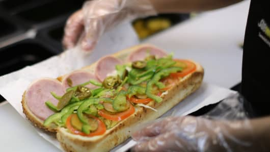A Subway sandwich artist making a sandwich.