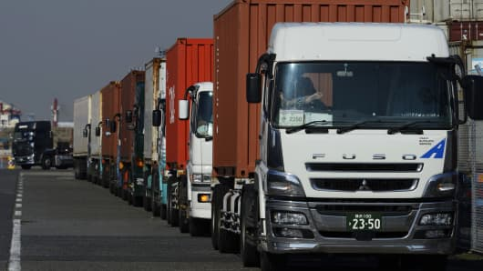 Trucks carrying containers wait in line at a shipping terminal in Yokohama City, Kanagawa Prefecture, Japan