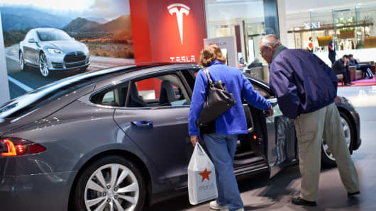 A couple look inside a Tesla Motors Inc. Model S at the company's store at the Short Hills Mall in Short Hills, New Jersey.
