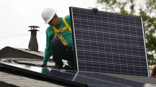 A SolarCity employee installs a solar panel on the roof of a home in the Eagle Rock neighborhood of Los Angeles.