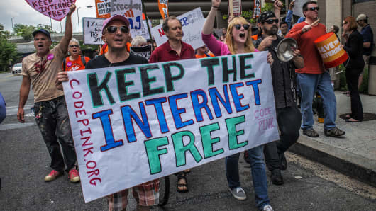 Protesters march past the FCC headquarters before the Commission meeting on net neutrality proposal on May, 15, 2014 in Washington, DC