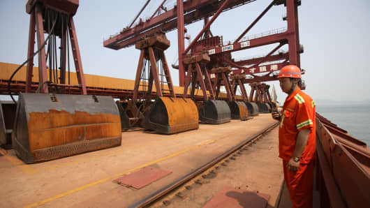 A dock worker inspects large diggers used to transport iron ore at one of the terminals of the Qingdao Port in Qingdao, China.