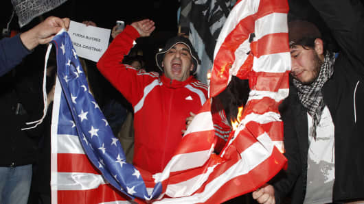 Demonstrators set fire on an U.S. flag during a protest near the United States embassy in Buenos Aires June 17, 2014.