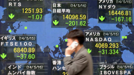 A man walks past an electronic stock indicator at the window of a security company in Tokyo on May 16, 2014.