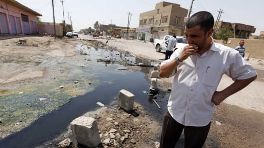 In this file photo, a man stands in a sewage-filled street in Fallujah, Iraq, 40 miles (65 kilometers) west of Baghdad. Ten years and $60 billion in taxpayer funds later, Iraq is still so unstable and broken that even its leaders question whether U.S. efforts to rebuild it were worth the cost.