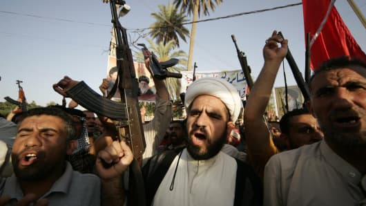 Tribal fighters shout slogans while carrying weapons during a parade in Kerbala, south of Baghdad, June 18, 2014.