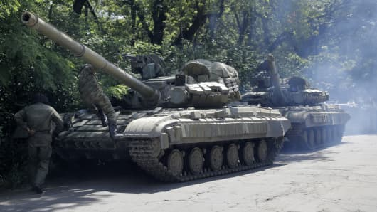 Troops from a pro-Russian militia prepare to travel in a tank on a road near the town of Yanakiyevo, Donetsk region, eastern Ukraine, Friday, June 20, 2014.