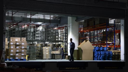 A worker walks in front of a storage area in a logistics center at the Pudong free trade zone in Shanghai, China.