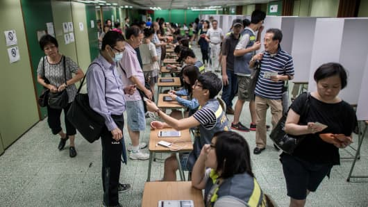 A volunteer hands a voter's ID card at a polling station in Hong Kong on June 22, 2014.