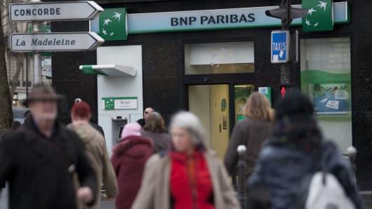 Pedestrians pass a branch of BNP Paribas SA bank in Paris, France.