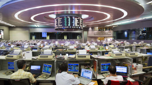Stock traders sit at their desks facing an electronic board on the trading floor of the Hong Kong Stock Exchange in Hong Kong, China.