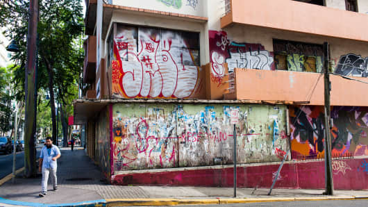 A man walks past a vacant building in the Santurce neighborhood of San Juan, Puerto Rico.