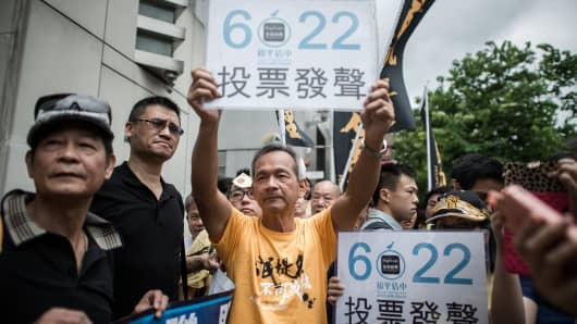 Demonstrators supporting the 'occupy central' movement display placards asking residents to cast ballots for the referendum on three proposals outlining rules for the chief executive election.