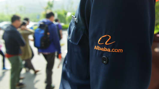 Members of staff walk past a security guard at the headquarters of the Alibaba Group in Hangzhou, China.