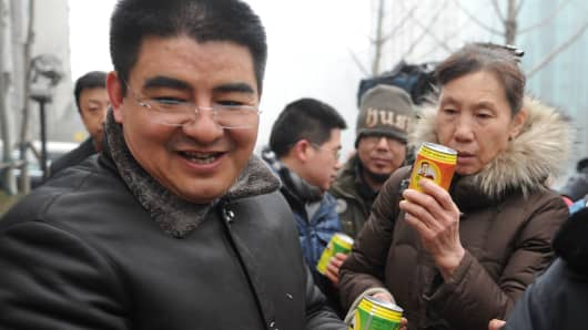 Chen Guangbiao (C), Chairman of Jiangsu Huangpu Recycling Resources Co., Ltd, presents his company's product canned fresh air at Beijing Financial Street on January 30, 2013 in Beijing, China.