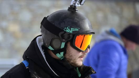 A skier carrying a GoPro camera on his helmet.